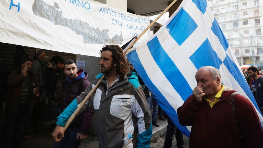 A protester holds a Greek flag as farmers gather outside the Greek Agriculture Ministry, in Athens, Wednesday, March 8, 2017. Several hundred farmers from the island of Crete are protesting against government tax reforms tied to the country's international bailout. (AP Photo/Thanassis Stavrakis)