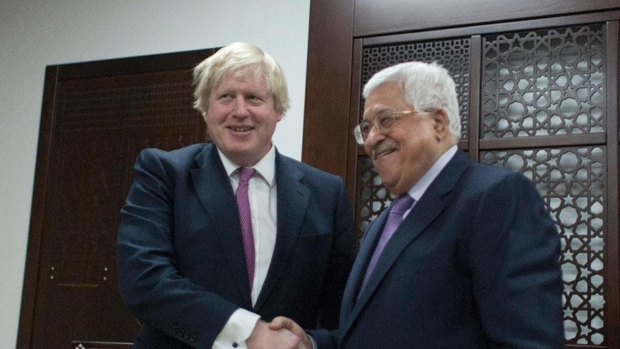 Palestinian President Mahmoud Abbas, right, shakes hands with Britain's Foreign Secretary Boris Johnson during their meeting, in the West Bank city of Ramallah, Wednesday, March 8, 2017. (AP Photo/Nasser Nasser)