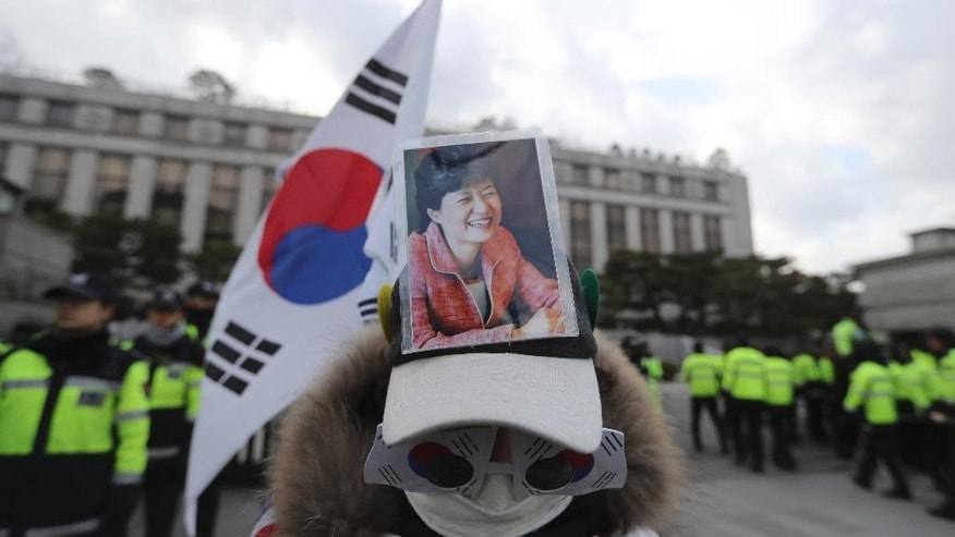 A supporter of impeached South Korean President Park Geun-hye wearing a hat with a picture of President Park, stands with a national flag in front of the Constitutional Court in Seoul, South Korea, Wednesday, March 8, 2017. South Korea's highest court says it will rule this week on whether impeached President Park Geun-hye should permanently step down over a corruption scandal or be reinstated to office. (AP Photo/Lee Jin-man)