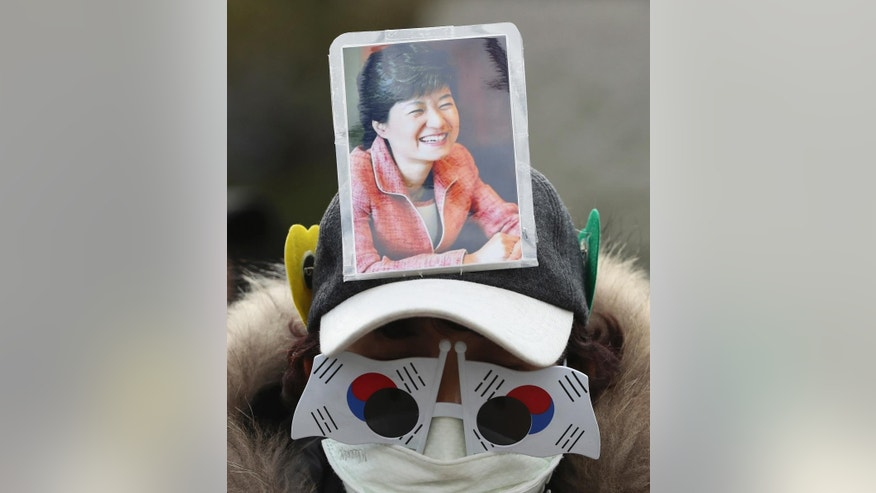 A supporter of impeached South Korean President Park Geun-hye wearing a hat with a picture of President Park and wearing the South Korean flags on glasses, stands in front of the Constitutional Court in Seoul, South Korea, Wednesday, March 8, 2017. South Korea's highest court says it will rule this week on whether impeached President Park Geun-hye should permanently step down over a corruption scandal or be reinstated to office. (AP Photo/Lee Jin-man)