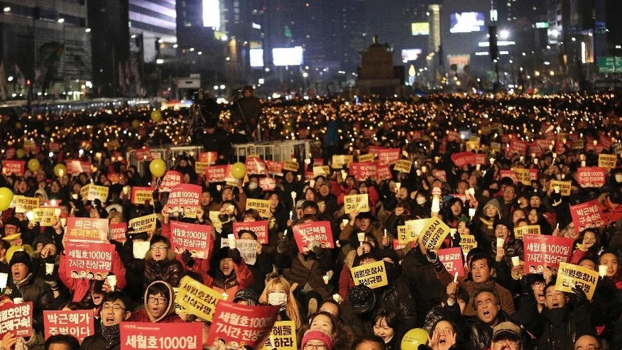 "FILE - In this Jan. 7, 2017 file photo, Protesters shout slogans during a candle light vigil calling for impeached President Park Geun-hye to step down in Seoul, South Korea. South Korea's highest court said Wednesday it will rule this week on whether impeached President Park Geun-hye should permanently step down over a corruption scandal or be reinstated, a decision that could radically reshape the country's political landscape. The signs read ""Arrest Park Geun-hye."" (AP Photo/Ahn Young-joon, File)"