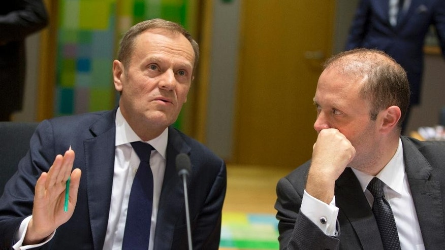 European Council President Donald Tusk, left, speaks with Malta's Prime Minister Joseph Muscat as they wait for the start of a pre-EU summit Tripartite meeting at the Europa building in Brussels on Wednesday, March 8, 2017. Donald Tusk is closing in on a second term as the European Union's Council President despite fierce opposition from his native Poland, whose most influential politician is a bitter rival of the former prime minister. (AP Photo/Virginia Mayo)