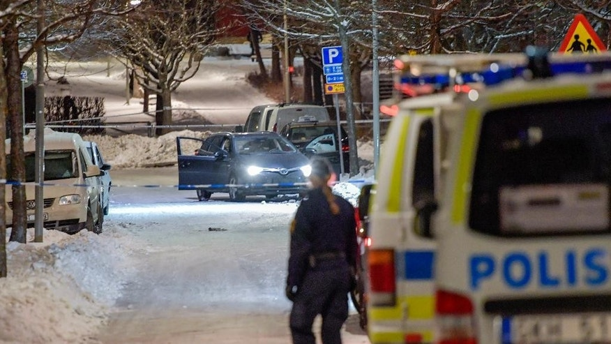 A police officer looks at a car behind a police cordon, in Stockholm, Sweden, late Wednesday March 8, 2017. Swedish police say two men in their 20s have been shot dead while sitting in a car in a Stockholm suburb where feuds between criminal gangs fighting over territory have taken place. (Jessica Gow/TT News Agency via AP)