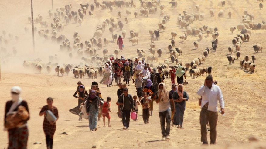 August 10, 2014: Displaced people from the minority Yazidi sect, fleeing violence from forces loyal to the Islamic State in Sinjar town, walk towards the Syrian border, on the outskirts of Mt. Sinjar.