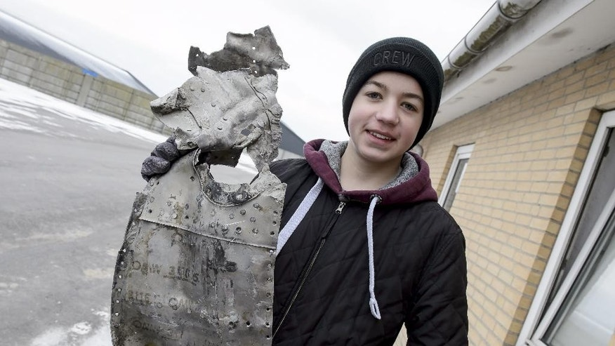 In this Tuesday, March 7, 2017 photo, Danish teenager, Rom Kristiansen, holds up a piece of the wreckage from a World War II airplane that likely crashed in a northern Denmark mire 72 years ago _ which he found, near Birkelse, Denmark. A Danish teenager has found parts of a German World War II airplane that likely crashed in a northern Denmark swamp 72 years ago — including the remains of a man who might have been its pilot. (Rene Schuetze/Polfoto via AP)