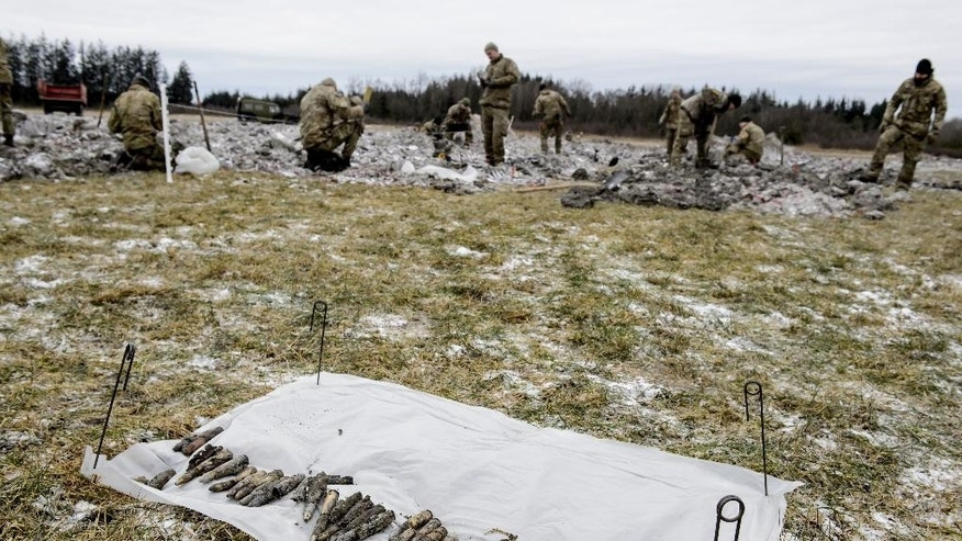 In this Wednesday, March 8, 2017 photo, members of the Danish military check for wreckage from a World War II airplane  which was found, by teenager Rom Kristiansen, near Birkelse, Denmark. A Danish teenager has found parts of a German World War II airplane that likely crashed in a northern Denmark swamp 72 years ago — including the remains of a man who might have been its pilot.  (Rene Schuetze/Polfoto via AP)