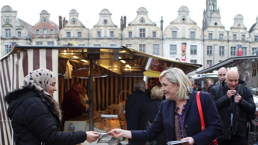 FILE - In this Nov. 7, 2015 file photo, French far-right leader Marine Le Pen hands out leaflets in a marketplace, in Arras northern France, as part of her municipal campaign. Ex-communists and others who converted from the political left are among those campaigning for far-right candidate Marine Le Pen in France's presidential election. Her party is highlighting their switch of sides to push home its argument that traditional left-right politics are dead and to convince more voters to make a similar leap. (AP Photo/Michel Spingler, File)