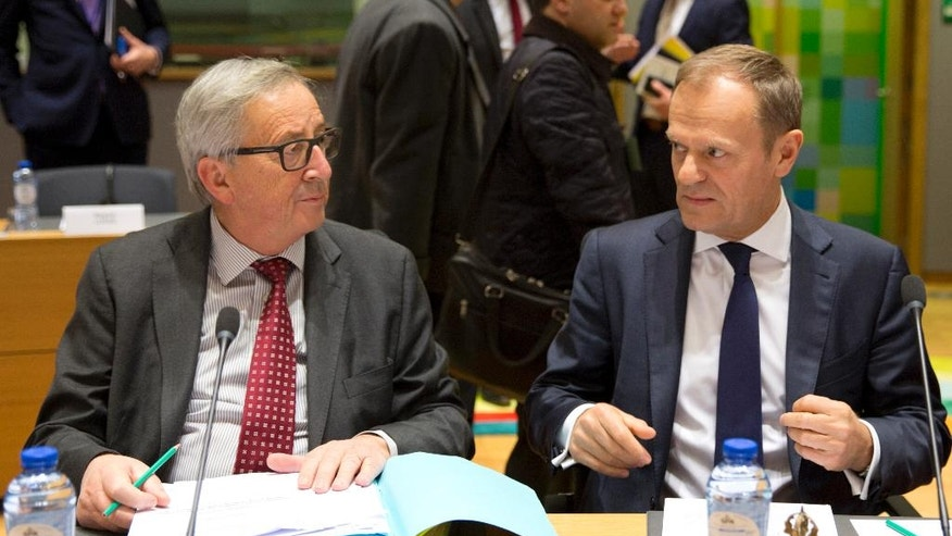 European Commission President Jean-Claude Juncker, left, speaks with European Council President Donald Tusk as they wait for the start of a pre-EU summit Tripartite meeting at the Europa building in Brussels on Wednesday, March 8, 2017. Donald Tusk is closing in on a second term as the European Union's Council President despite fierce opposition from his native Poland, whose most influential politician is a bitter rival of the former prime minister. (AP Photo/Virginia Mayo)