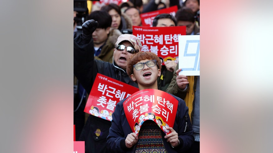 "Protesters shout slogans during a rally calling for impeachment of President Park Geun-hye near the Constitutional Court in Seoul, South Korea, Friday, March 10, 2017. People gathered Friday ahead of a court ruling on whether impeached Park will be removed from office over a corruption scandal or allowed to complete her term. The letters read ""Impeachment, Park Geun-hye."" (AP Photo/Lee Jin-man)"