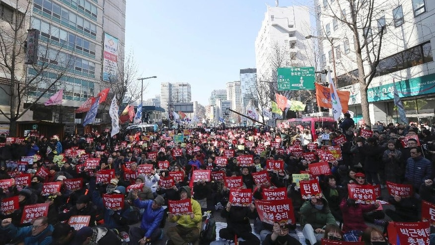 "Protesters shout slogans during a rally calling for impeachment of President Park Geun-hye near the Constitutional Court in Seoul, South Korea, Friday, March 10, 2017. Sensing history, hundreds of people gathered Friday ahead of a court ruling on whether impeached South Korean President Park will be removed from office over a corruption scandal or allowed to complete her term. The letters read ""Impeachment, Park Geun-hye."" (AP Photo/Lee Jin-man)"