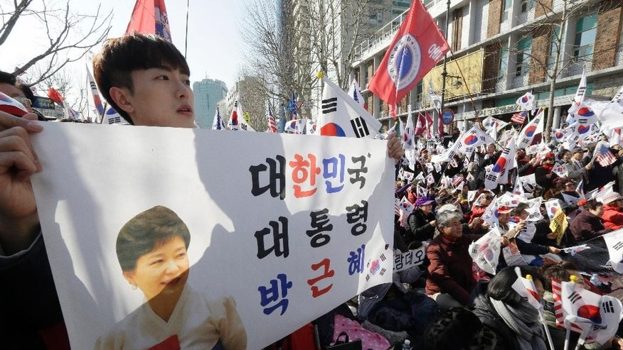 "Supporters of South Korean President Park Geun-hye stage a rally opposing her impeachment near the Constitutional Court in Seoul, South Korea, Friday, March 10, 2017. People gathered Friday ahead of a court ruling on whether impeached Park will be removed from office over a corruption scandal or allowed to complete her term. The sign reads "" South Koran President Park Geun-hye."" (AP Photo/Ahn Young-joon)"