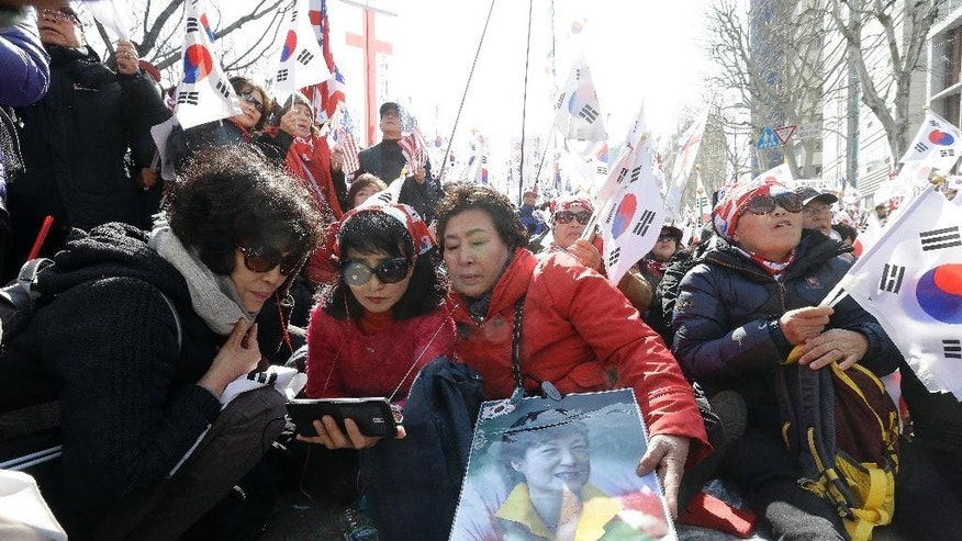 Supporters of South Korean President Park Geun-hye watch a broadcast live of a Constitutional Court decision on a smart phone during a rally opposing her impeachment near the Constitutional Court in Seoul, South Korea, Friday, March 10, 2017. (AP Photo/Ahn Young-joon)