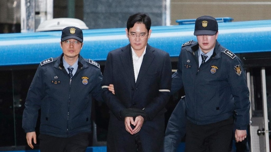 FILE - In this Feb. 22, 2017, file photo, Lee Jae-yong, center, vice chairman of Samsung Electronics Co., arrives at the office of the independent counsel in Seoul, South Korea. Samsung lawyers have denied all charges brought against Lee Jae-yong, the billionaire heir to Samsung, in a massive corruption scandal that has ensnared the country's president. (AP Photo/Ahn Young-joon, File)
