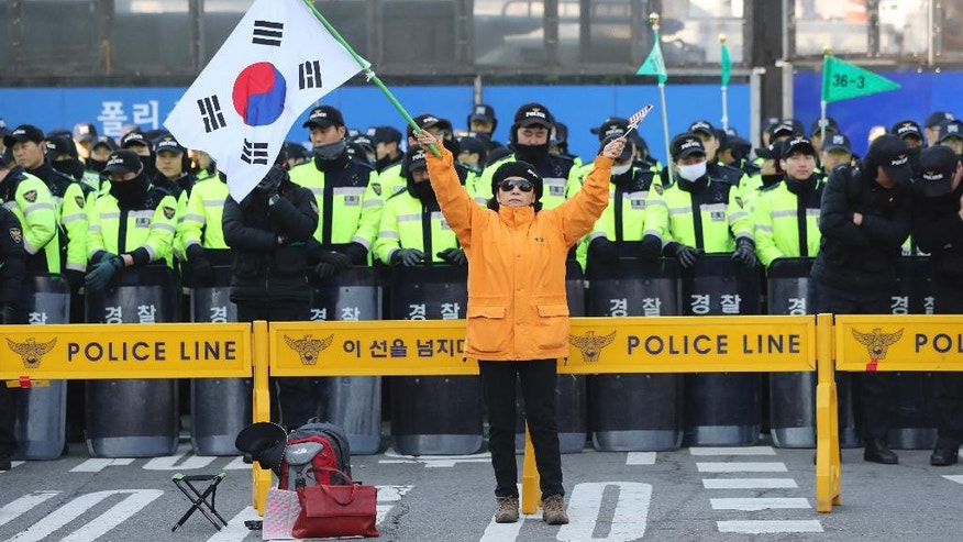 A supporter of impeached South Korean President Park Geun-hye holds a national flag as police officers stand guard near the Constitutional Court in Seoul, South Korea, Thursday, March 9, 2017. South Korea's Constitutional Court will rule Friday on whether impeached President Park Geun-hye should permanently leave office over a corruption scandal or be reinstated, a decision that could radically reshape the country's political landscape. (AP Photo/Lee Jin-man)