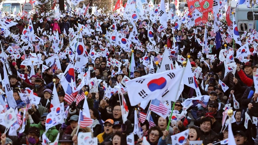 Supporter of impeached South Korean President Park Geun-hye wave national flags during a rally opposing her impeachment near the Constitutional Court in Seoul, South Korea, Thursday, March 9, 2017. South Korea's Constitutional Court will rule Friday on whether impeached President Park Geun-hye should permanently leave office over a corruption scandal or be reinstated, a decision that could radically reshape the country's political landscape. (AP Photo/Lee Jin-man)