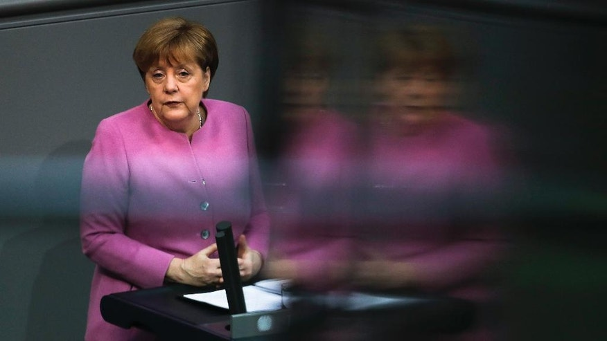 In this photo taken with reflections in windows of the visitors tribune German Chancellor Angela Merkel delivers a speech on Europe ahead of an EU summit in Brussels at the German parliament Bundestag in Berlin, Germany, Thursday, March 9, 2017. (AP Photo/Markus Schreiber)