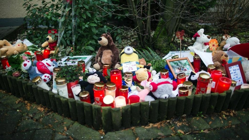 Soft toys, candles and flowers are placed in front of a house in Herne, Germany, Wednesday, March 8, 2017, where the body of a nine-year-old boy was found. German police hunting for a 19-year-old man believed to have slain the neighbor's child say they have not yet found any evidence of a second crime despite an online claim. (Marcel Kusch/dpa via AP)