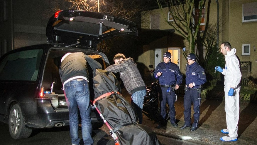 Undertakers lift a stretcher with a bodybag into a hearse in Herne, Germany, Tuesday, March 7, 2017. German police said Tuesday they have launched a manhunt for a 19-year-old man who allegedly killed a 9-year-old boy in the western town of Herne and boasted about the murder on a video posted online. (Marcel Kusch/dpa via AP)