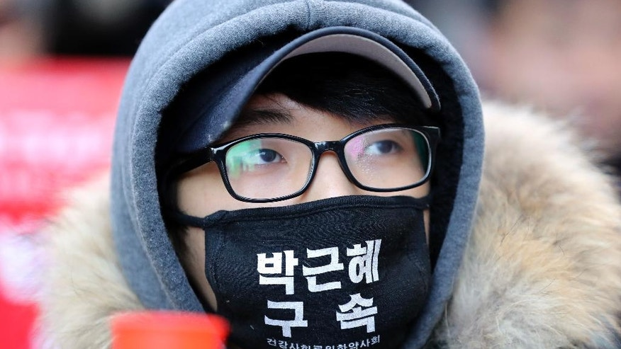 "A protester wearing a mask, attends during a rally calling for impeachment of President Park Geun-hye near the Constitutional Court in Seoul, South Korea, Friday, March 10, 2017. People gathered Friday ahead of a court ruling on whether impeached Park will be removed from office over a corruption scandal or allowed to complete her term. The letters read ""Arrest Park Geun-hye."" (AP Photo/Lee Jin-man)"
