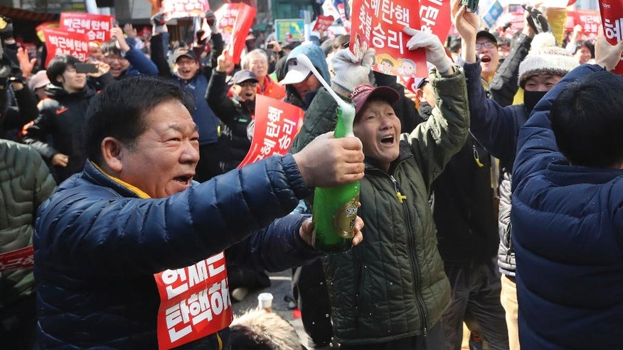 A protester opens a bottle of champagne to celebrate after hearing the Constitutional Court's verdict during a rally calling for impeachment of President Park Geun-hye near the Constitutional Court in Seoul, South Korea, Friday, March 10, 2017. In a historic ruling Friday, South Korea's Constitutional Court formally removed impeached President Park Geun-hye from office over a corruption scandal that has plunged the country into political turmoil, worsened an already-serious national divide and led to calls for sweeping reforms. (AP Photo/Lee Jin-man)