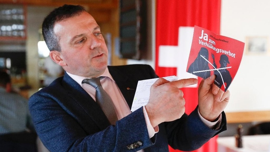 "FILE - In this  Feb. 12, 2017 file photo National Councillor Walter Wobmann displays a leaflet reading ""Yes to the ban on veiling'' at the reunion of the Swiss People's Party SVP in Dornach, Switzerland.  Switzerland's upper house of parliament has rejected an initiative championed by the right-wing populist party to ban burqas, the face- and body-covering garment worn by some Muslim women.  The Council of State voted 26-9 with four abstentions Thursday  March 9, 2017 against the measure that narrowly passed the lower house in November.  (Peter Klaunzer/Keystone via AP, file)"