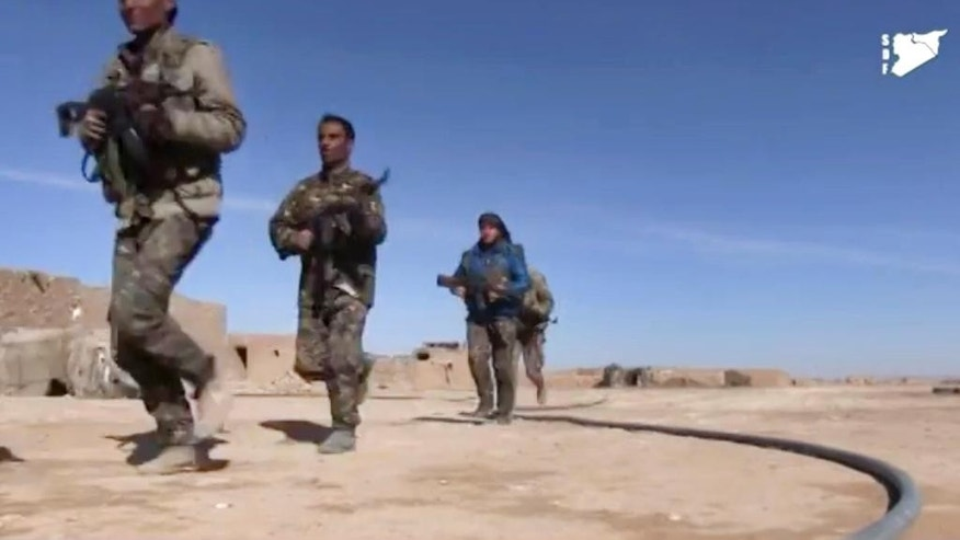 FILE - This file frame grab from a video provided on Monday, March 6, 2017 by the Syria Democratic Forces (SDF), shows fighters from the SDF running during fighting with Islamic State group militant, in Raqqa's eastern countryside, Syria. The Kurdish-led Syrian Democratic Forces is likely to lead the operation to capture the northern Syrian city of Raqqa from the Islamic State group in the coming weeks as the forces presses in its offensive against the extremists in areas close to their de facto capital. (Syria Democratic Forces, via AP, File)