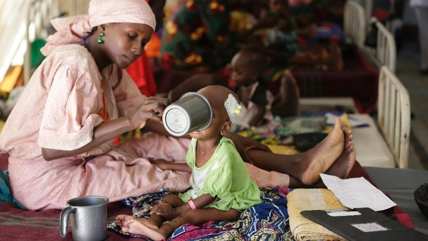 "FILE - In this Monday, Aug. 29, 2016 file photo, a mother feeds her malnourished child at a feeding centre run by Doctors Without Borders in Maiduguri, Nigeria. The United Nations children's agency warned Tuesday, Feb. 21, 2017 that almost 1.4 million children are at ""imminent risk of death"" as famine threatens parts of South Sudan, Nigeria, Somalia and Yemen. (AP Photo/Sunday Alamba, File)"