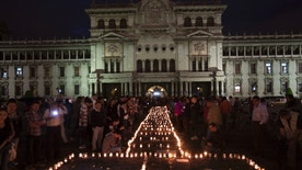 People hold a candlelight vigil outside the National Palace in remembrance of the girls who died in a fire at the Virgin of the Assumption Safe Home in Guatemala City, Thursday, March 9, 2017. A blaze that killed at least 34 girls at a shelter for troubled youths erupted when some of them set fire to mattresses to protest rapes and other mistreatment at the badly overcrowded institution, the parent of one victim said Thursday.  (AP Photo/Moises Castillo)