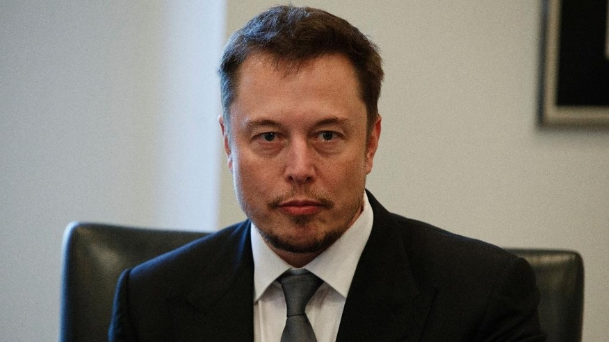 FILE - In this Dec. 14, 2016, file photo, Tesla CEO Elon Musk listens as President-elect Donald Trump speaks during a meeting with technology industry leaders at Trump Tower in New York., Musk promised on Twitter March 9, 2017, to solve an energy crisis in Australia or his company's services are free. (AP Photo/Evan Vucci, File)