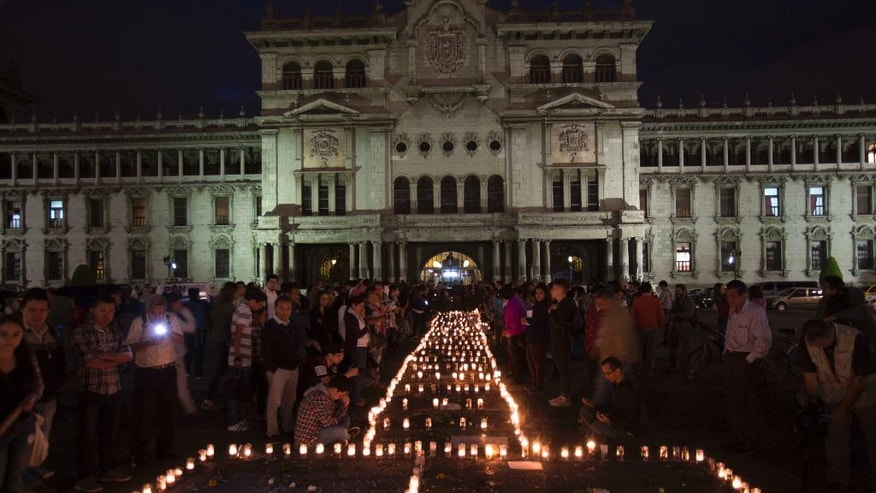 People hold a candlelight vigil outside the National Palace in remembrance of the girls who died in a fire at the Virgin of the Assumption Safe Home in Guatemala City, Thursday, March 9, 2017. A blaze, that killed at least 35 girls at a shelter for troubled youths, erupted when some of them set fire to mattresses to protest rapes and other mistreatment at the badly overcrowded institution, the parent of one victim said Thursday.  (AP Photo/Moises Castillo)