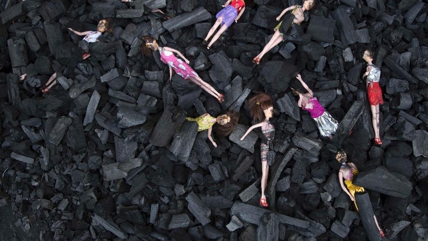 Charred-stained dolls placed on a bed of charcoal is part of artists' installation placed at the front gate of Presidential House, in remembrance of the victims of a fire at a youth children, in Guatemala City, Thursday, March 9, 2017. Hospital officials say the death toll in the Wednesday morning fire at the Virgin of the Assumption Safe Home has risen to 28 after several more girls died overnight of severe burns. (AP Photo/Luis Soto)