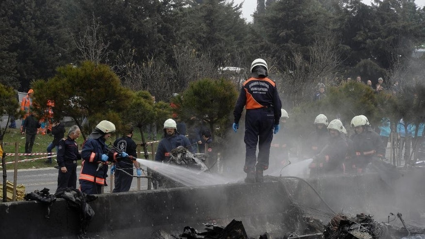 Firefighters work on the site shortly after a helicopter with seven people inside was crashed in Istanbul's Buyukcekmece district, Friday, March 10, 2017. A helicopter crashed on a highway in the outskirts of Istanbul on Friday, after apparently hitting a television tower in dense fog, reports said. At least five people were killed, the governor said. (IHA via AP)