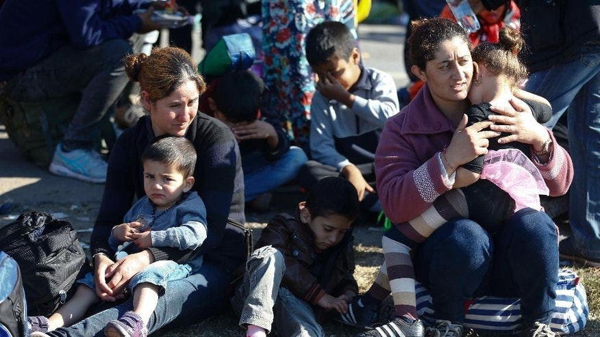 "FILE - In this Sept. 9. 2015 file photo a group of migrants rest near the Hungarian border with Serbia, in Roszke, southern Hungary. A spokesman for Hungary's governing Fidesz party says Wednesday March 8, 2017 its lawmakers will likely submit a new law regulating nongovernmental organizations within two weeks. Fidesz spokesman Janos Halasz says the law is aimed at revealing the foreign funding received by ""agent organizations"" seeking to influence Hungarian politics.   (AP Photo/Matthias Schrader, file)"