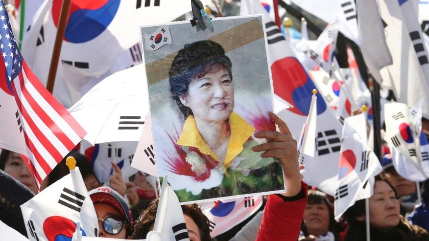 A supporter of South Korean President Park Geun-hye holds up her portrait during a rally opposing her impeachment in Seoul, South Korea, Friday, March 10, 2017. In a historic ruling Friday, South Korea's Constitutional Court formally removed the impeached president from office over a corruption scandal that has plunged the country into political turmoil, worsened an already-serious national divide and led to calls for sweeping reforms. (AP Photo/Ahn Young-joon)