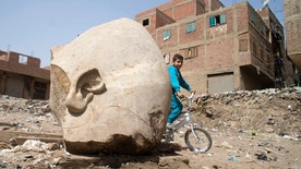 A boy rides his his bicycle past a recently discovered statue in a Cairo slum that may be of pharaoh Ramses II, in Cairo, Egypt, Friday, March 10, 2017. Archeologists in Egypt have discovered a massive statue that may be of pharaoh Ramses II, one of the country's most famous ancient rulers. The colossus, whose head was pulled from mud and groundwater by a bulldozer on Thursday, is around eight meters (yards) tall and was discovered by a German-Egyptian team. (AP Photo/Amr Nabil)