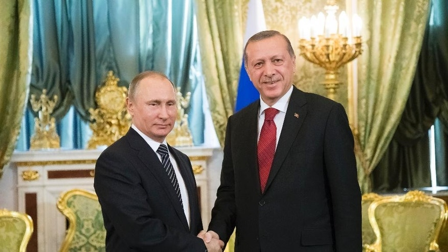 Russian President Vladimir Putin, left, shakes hands with Turkey's President Recep Tayyip Erdogan during their meeting in the Kremlin in Moscow, Russia, Friday, March 10, 2017. The talks focused on Syria, where Russia and Turkey have launched a joint mediation effort and coordinated their military action against the Islamic State group. (AP Photo/Alexander Zemlianichenko, pool)
