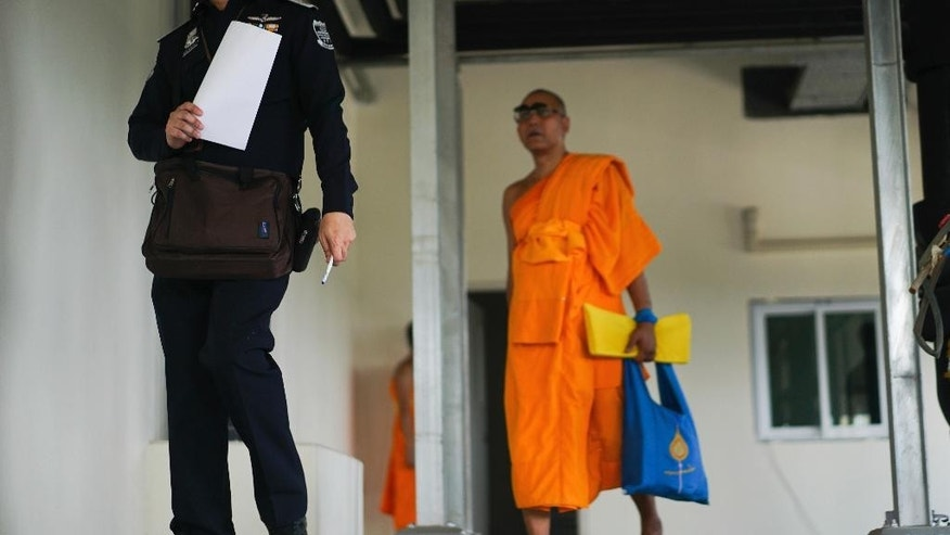A monk follows an officer inspecting a medical center on the Wat Dhammakaya temple compound in Pathum Thani province, Thailand, Friday, March 10, 2017. Thai police have concluded a weeks-long search for the controversial Buddhist temple's senior monk, wanted on criminal charges over tens of millions in embezzled money. (AP Photo/Dake Kang)