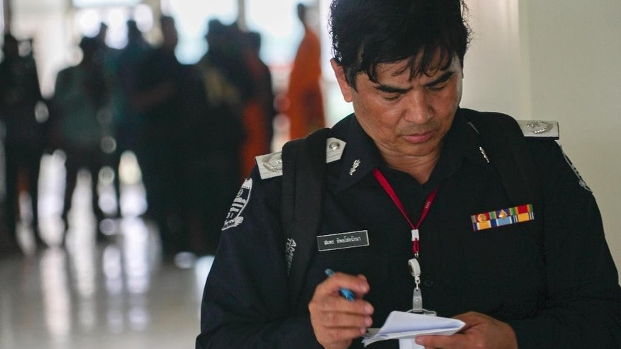 An officer checks his notes inside a medical center on the Wat Dhammakaya temple compound in Pathum Thani province, Thailand, Friday, March 10, 2017. Thai police have concluded a weeks-long search for the controversial Buddhist temple's senior monk, wanted on criminal charges over tens of millions in embezzled money. (AP Photo/Dake Kang)