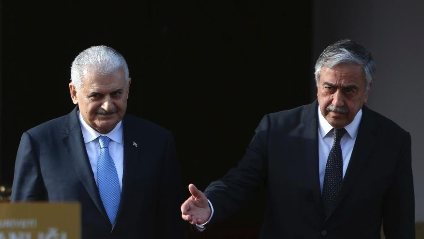 Turkey's Prime Minister Binali Yildirim, left, and Turkish Cypriot leader Mustafa Akinci leave their meeting for the  press conference in the Turkish Cypriot breakaway northern part of the divided capital Nicosia, Cyprus, Thursday, March 9, 2017. Yildirim is in the breakaway north part of the island for a one-day visit for talks. (AP Photo/Petros Karadjias)
