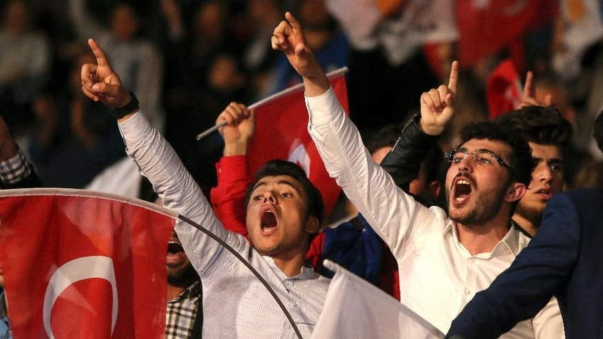 Supporters of the Turkish President Recep Tayyip Erdogan shout slogans as Turkey's Prime Minister Binali Yildirim addresses voters during a rally to shore up support for a 'yes' vote in next month's referendum in Turkey on expanding presidential powers, at a stadium in Nicosia, Cyprus, Thursday, March 9, 2017. Turkish officials have said there are as many as 100,000 voters eligible to cast a vote in the April 16 poll in the breakaway Turkish Cypriot north of ethnically divided Cyprus. (AP Photo/Petros Karadjias)