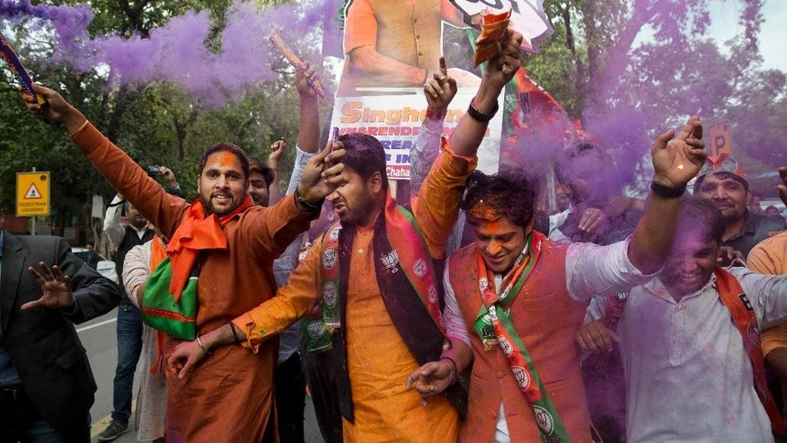 CORRECTS LOCATION SPELLING: Bharatiya Janata Party (BJP) supporters celebrate as their party leads in state elections in Uttarakhand and Uttar Pradesh states in New Delhi, India, Saturday, March 11, 2017. India's governing Hindu nationalist party is heading for major victories in key state legislature elections that are seen as a referendum on Prime Minister Narendra Modi's nearly 3-year-old rule. (AP Photo/Tsering Topgyal)