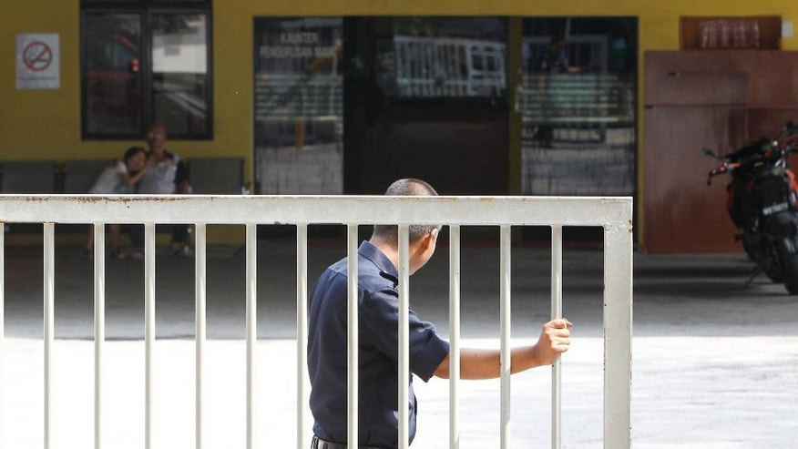 A police officer closes the main gate of forensic department at Kuala Lumpur Hospital in Kuala Lumpur, Malaysia Saturday, March 11, 2017. Malaysian police on Friday formally identified Kim Jong Nam as the victim of a fatal nerve agent attack at Kuala Lumpur's airport, an expected but significant development in a case that has broken down the once-warm ties between North Korea and Malaysia. (AP Photo/Daniel Chan)