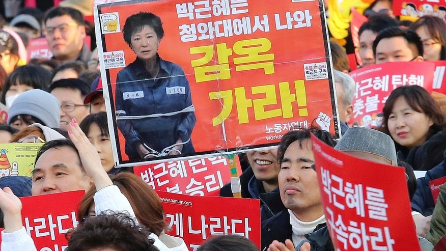 "Protesters attend a rally calling for impeached President Park Geun-hye's arrest in Seoul, South Korea, Saturday, March 11, 2017. South Korean police on Saturday braced for more violence between opponents and supporters of ousted President Park Geun-hye, who was stripped of her powers by the Constitutional Court over a corruption scandal that has plunged the country into a political turmoil. The signs read "" Go to prison."" (AP Photo/Ahn Young-joon)"