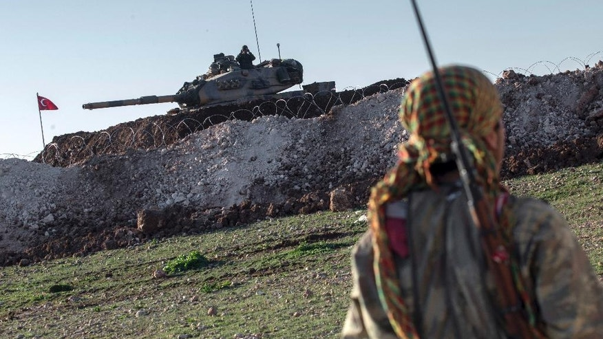 FILE - In this February 22, 2015, file photo, a Syrian Kurdish militia member of the YPG patrols near a Turkish army tank as Turks work to build a new Ottoman tomb in the background in Esme village in Aleppo province, Syria. Turkey's military incursion in northern Syria succeeded in gaining it a foothold and driving Islamic State group militants away from its border _ but its determination to also push back the Kurds is causing it trouble. (AP Photo/Mursel Coban, Depo Photos, File)