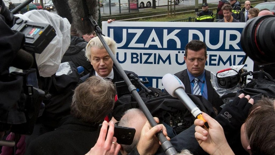 "Campaign staff hold a banner reading ""Stay Away, This Is Our Country"" as firebrand anti Islam lawmaker Geert Wilders, left, protests outside the Turkish embassy in The Hague, Netherlands, Wednesday, March 8, 2017, against the planned campaign visit of Turkish Foreign Minister Mevlut Cavusoglu to lobby for a referendum giving President Erdogan increased powers. (AP Photo/Peter Dejong)"