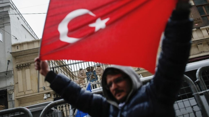"A Turkish man holds up a national flag outside the Dutch consulate in Istanbul, Sunday, March 12, 2017. The escalating dispute between Turkey and the Netherlands spilled over into Sunday, with a Turkish minister unable to enter her consulate after the authorities there had already blocked a visit by the foreign minister, prompting Turkish President Recep Tayyip Erdogan to call the Dutch "" fascists."" (AP Photo/ Emrah Gurel)"