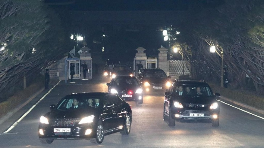 A vehicle, front left, carrying ousted South Korea's former President Park Geun-hye, center in the car,  leaves from the presidential Blue House to her private home in Seoul. South Korea, Sunday, March 12, 2017. Park left the presidential palace on Sunday evening, two days after the country's Constitutional Court removed her from office over a massive corruption scandal. (Baek Seung-yul/Yonhap via AP)