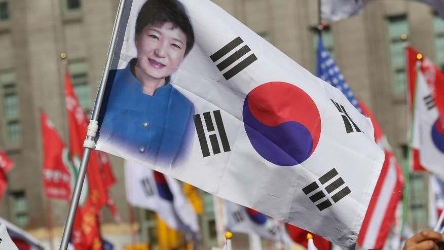 FILE - In this Saturday, Feb. 25, 2017, file photo, a South Korean national flag with a picture of impeached South Korean President Park Geun-hye is seen during a rally opposing her impeachment in Seoul, South Korea. Hundreds of police officers, reporters and supporters of the ousted president have gathered near her Seoul home in anticipation of her return from the presidential palace. An official from the presidential Blue House said Sunday, March 12, that there was a possibility that Park would leave during the evening, two days after the country's Constitutional Court removed her from office over a corruption scandal. (AP Photo/Lee Jin-man, File)