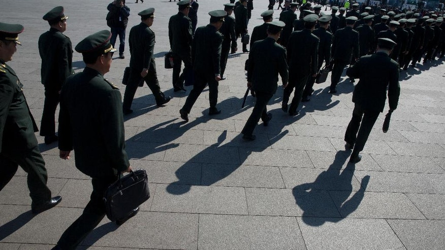 In this photo taken Wednesday, March 8, 2017, Chinese military officers file into near the Great Hall of the People where a plenary session of the National People's Congress is held in Beijing, China. China's ceremonial parliament and its official advisory body traditionally hold their annual sessions at Beijing's Great Hall of the People during the first two weeks of March, a time when the Chinese capital is finally emerging from the long winter freeze. This year's gatherings were blessed by unusually clear weather, with little of the choking smog that so often grips the capital, and the resulting sunshine cast heavy black shadows of the building and people on the surrounding plaza.(AP Photo/Ng Han Guan)