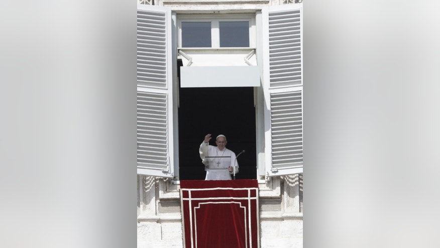 Pope Francis waves to faithful during the Angelus prayer he delivered from his studio overlooking St. Peter's Square at the Vatican, Sunday, March 12, 2017. (AP Photo/Gregorio Borgia)